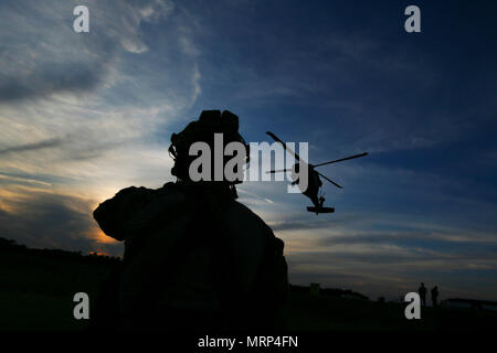 A U.S. Air Force tactical air control party airman from the 227th Air Support Operations Squadron watches a hovering UH-60 Black Hawk helicopter during joint training for New Jersey Task Force One at Joint Base McGuire-Dix-Lakehurst, N.J., June 28, 2017. The primary mission of New Jersey Task Force One is to provide advanced technical search and rescue capabilities to victims trapped or entombed in structurally collapsed buildings. Task Force One is made up of New Jersey National Guard Soldiers and Airmen, as well as civilians. (U.S. Air National Guard photo by Master Sgt. Matt Hecht/Released) - Stock Photo