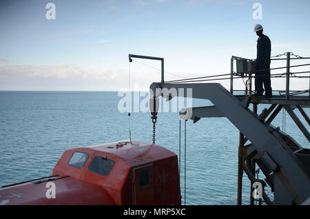 170630-N-WJ640-006 NOUMEA, New Caledonia (June 30, 2017) Andre Sutton, Boatswain onboard USNS Sacagawea (T-AKE 2), participates in life boat testing and maintenance off shore Noumea, New Caledonia in support of Koa Moana 17, June 30. Koa Moana 17 is designed to improve theater security, and conduct law enforcement and infantry training in the Pacific region in order to enhance interoperability with partner nations. (U.S. Navy photo by Mass Communication Specialist 3rd Class Madailein Abbott) - Stock Photo