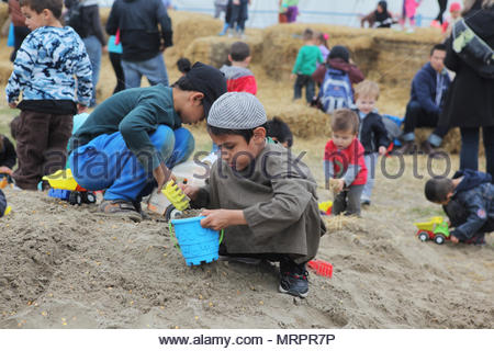 Children playing in large sandbox in Markham, Ontario, Canada. - Stock Photo