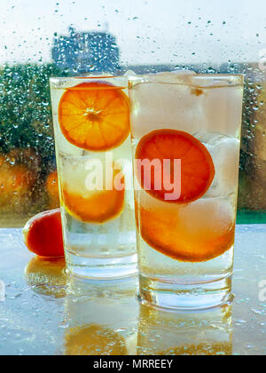 a glass of detox with tangerine and ice, next to a box of tangerines, Detox, breakfast and healthy lifestyle concept. - Stock Photo