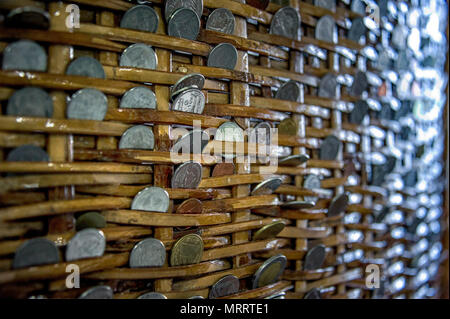 Coins in a basket. Money in a basket. Coins of various types and values inserted in between the woven of rattan basket. - Stock Photo