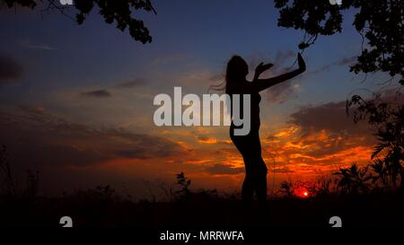 Female silhouette meditating in evening and doing yoga in sunset background. - Stock Photo
