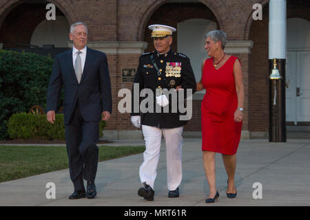 From left, Secretary James N. Mattis, Department ofDefense, Commandant of the Marine Corps Gen. Robert B. Neller, and D'Arcy Neller walk down center walk during an evening parade at Marine Barracks Washington, Washington, D.C., June 30, 2017. Neller hosted the parade and Mattis was the guest of honor. (U.S. Marine Corps photo by Cpl. Samantha K. Braun) - Stock Photo