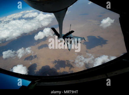 A French air force Rafale receives fuel from a 340th Expeditionary Air Refueling Squadron KC-135 Stratotanker in support of Operation Inherent Resolve, July 1, 2017.Rafale is a French twin-engine, canard delta wing, multirole fighter aircraft with a wide range of weapons. The Rafale is intended to perform air supremacy, interdiction, aerial reconnaissance, ground support, in-depth strike and anti-ship strike missions. (U.S. Air Force photo by Staff Sgt. Michael Battles) - Stock Photo