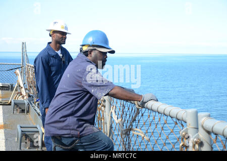 170706-N-WJ640-024 NOUMEA, New Caledonia (July 06, 2017) Andre Sutton, Boatswain onboard USNS Sacagawea (T-AKE 2) (left) and Aubery Barnes, Ordinary Seaman (right) assist in onloading supplies during stores onload off shore Noumea, New Caledonia in support of Koa Moana 17, July 6. Koa Moana 17 is designed to improve theater security, and conduct law enforcement and infantry training in the Pacific region in order to enhance interoperability with partner nations. (U.S. Navy photo by Mass Communication Specialist 3rd Class Madailein Abbott) - Stock Photo