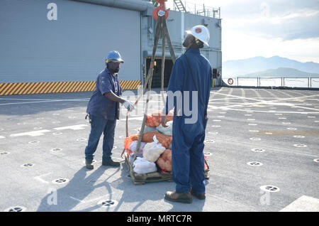 170706-N-WJ640-032 NOUMEA, New Caledonia (July 06, 2017) Andre Sutton, Boatswain onboard USNS Sacagawea (T-AKE 2) (right) and Aubery Barnes, Ordinary Seaman (left) assist in onloading supplies during stores onload off shore Noumea, New Caledonia in support of Koa Moana 17, July 6. Koa Moana 17 is designed to improve theater security, and conduct law enforcement and infantry training in the Pacific region in order to enhance interoperability with partner nations. (U.S. Navy photo by Mass Communication Specialist 3rd Class Madailein Abbott) - Stock Photo