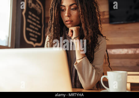 Closeup of a woman sitting at a restaurant table working on laptop. Freelancer sitting in cafe with a coffee working on laptop computer.