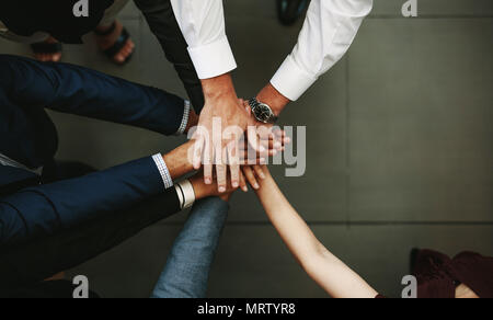 Unity and teamwork Concept. Top view of business people putting their hand together. - Stock Photo