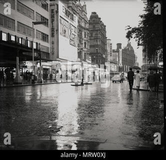 1960s, historical, view of a wet, damp, quite sparse leicester square, London, England, showing the Empire theatre, originally built in 1884 for variety theatre and then rebuilt in the 1920s for showing feature films. In 1961 Mecca bingo took over the Empire and turned it into an MGM cinema and a mecca dance hall. In this era traffic could go past the Empire, something that does not happen now. - Stock Photo