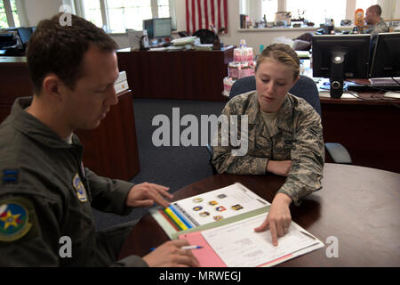 U.S. Air Force Airman 1st Class Stephanie Brogan (right), aviation resource management journeyman assigned to the 6th Operations Support Squadron, checks the record of an aircrew member at MacDill Air Force Base, Fla., July 6, 2017. Brogan's job includes tracking incentive pay and flight status. (U.S. Air Force photo by Airman 1st Class Rito Smith) - Stock Photo