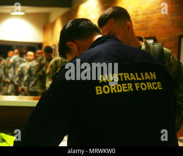 An Australian airport security official processes a Soldier assigned to the 1st Battalion 69th Infantry of the New York Army National Guard at Rockhampton, Australia on July 8, 2017. More than 800 New York Army National Guard members are in Australia to participate in Operation Talisman Sabre, a joint Australian-U.S. training exercise. ( U.S. Army National Guard photo by Sgt. Alexander Rector) - Stock Photo