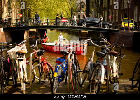 Amsterdam, Netherlands, April 24, 2015: Red Sightseeing Boat with captain passing underneath a bridge while people are crossing the bridge in Amsterda - Stock Photo