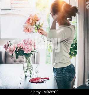 Shapely women arranging peonies bunch in glass vase on table at window with sunset light in living room. Lifestyle. Happy home - Stock Photo