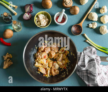 Chicken pieces with spices in wok frying pan on kitchen table with vegetables ingredients and wooden spoon, top view. Cooking preparation - Stock Photo