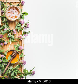 Honey in jar with dipper, honeycomb frame and wild flowers on white background, top view. Healthy  food, flat lay, border, vertical - Stock Photo