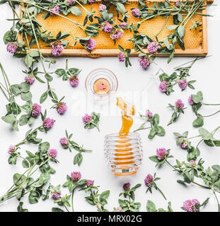 Honey poured from glass jar with dipper, honeycomb frame and wild flowers on white background, top view. Healthy  food, flat lay - Stock Photo