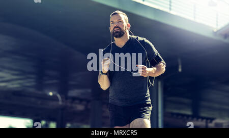 Fit young man in sportswear listening to music on earphones while running under a bridge during an urban run - Stock Photo
