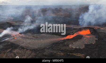 Lava and poisonous sulfur dioxide plumes rise as molten magma spews from a spatter cone at fissure 6 from the eruption of the Kilauea volcano May 25, 2018 in Pahoa, Hawaii. - Stock Photo