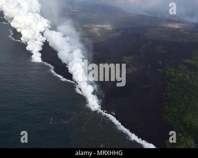 Lava and poisonous sulfur dioxide plumes rise as molten magma reaches the ocean from the eruption of the Kilauea volcano May 25, 2018 in Pahoa, Hawaii. Hot lava entering the ocean creates a dense white plume called 'laze' (short for 'lava haze'). Laze is formed as hot lava boils seawater to dryness. The process leads to a series of chemical reactions that create a billowing white cloud composed of a condensed seawater steam, hydrochloric acid gas, and tiny shards of volcanic glass. The cloud is as corrosive as dilute battery acid, and should be avoided. - Stock Photo