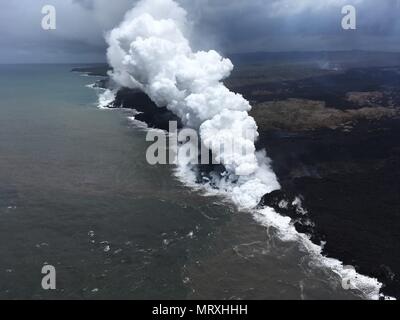 Lava and poisonous sulfur dioxide plumes rise as molten magma reaches the ocean from the eruption of the Kilauea volcano May 26, 2018 in Pahoa, Hawaii. Hot lava entering the ocean creates a dense white plume called 'laze' (short for 'lava haze'). Laze is formed as hot lava boils seawater to dryness. The process leads to a series of chemical reactions that create a billowing white cloud composed of a condensed seawater steam, hydrochloric acid gas, and tiny shards of volcanic glass. The cloud is as corrosive as dilute battery acid, and should be avoided. - Stock Photo