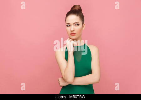 Pondering woman thinking, touching chin, looking up. Expression emotion and feelings concept. Studio shot, isolated on pink background - Stock Photo