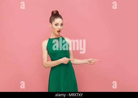Wow, look this way! Woman pointing finger at copy space. Expression emotion and feelings concept. Studio shot, isolated on pink background - Stock Photo