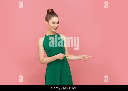 Woman toothy smiling and pointing finger at copy space. Expression emotion and feelings concept. Studio shot, isolated on pink background - Stock Photo