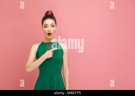 No way, look this ! Woman pointing finger at copy space. Expression emotion and feelings concept. Studio shot, isolated on pink background - Stock Photo