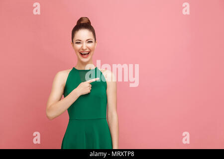 Handsome woman toothy smiling and pointing finger at copy space. Expression emotion and feelings concept. Studio shot, isolated on pink background - Stock Photo