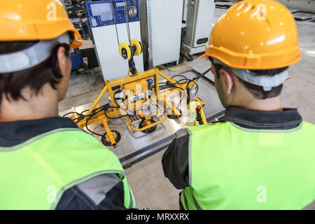 Workers near metal sheet lifting device at factory - Stock Photo