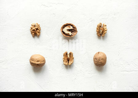 Walnuts on white background with shells and peeled as pattern, flat lay with copy space. - Stock Photo