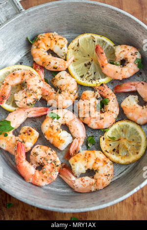 Roasted shrimps with lemon, garlic and herbs. Seafood, shelfish. Shrimps Prawns grilled with spices, garlic and lemon on black stone background, copy  - Stock Photo