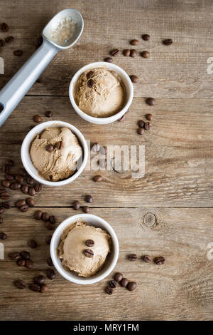 Coffee ice cream on wooden background, top view. Frozen coffee gelato ice cream with coffee beans and cinnamon - healthy summer dessert. - Stock Photo