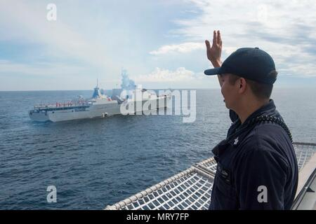 170710-N-PD309-206 SOUTH CHINA SEA (July 10, 2017) Gas Turbine System Technician (Mechanical) 1st Class Genesis Sulit waves to Vietnamese Gepard-class frigate Ly Thai To (HQ 012) aboard littoral combat ship USS Coronado (LCS 4) during a passing exercise as part of Naval Engagement Activity (NEA) Vietnam 2017. The engagement provides an opportunity for Sailors from the U.S. Navy and Vietnam People's Navy to interact and share knowledge to enhance mutual capabilities and strengthen solid partnerships. (U.S. Navy photo by Mass Communication Specialist 3rd Class Deven Leigh Ellis/Released) - Stock Photo