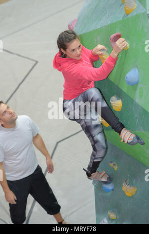 instructor watching woman climb indoor structure - Stock Photo