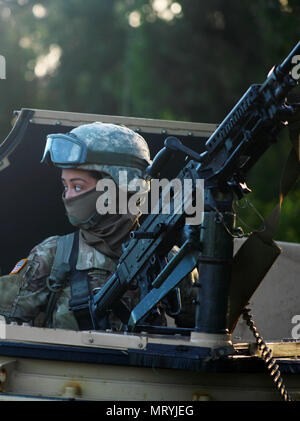 Sgt. Jeancarlo Galindo, a team leader assigned to Fox Company, 427th Brigade Support Battalion of the New York Army National Guard,  loads a M240B machine gun while preparing to go out on a patrol at Shoalwater Bay, Queensland, Australia, during exercise Talisman Saber, July 15. During the exercise, a series of war games, New York Army National Guard Soldiers fought against, and alongside Australian and New Zealand personnel. (U.S. Army National Guard photo by Sgt. Alexander Rector) - Stock Photo