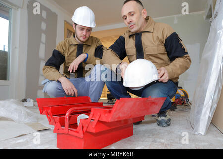 electrician with apprentice working in new home - Stock Photo