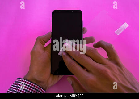 Hands of a young man holding and cleaning a mobile phone to put on a tempered glass. Protecting a smartphone, photo isolated on pink background. - Stock Photo