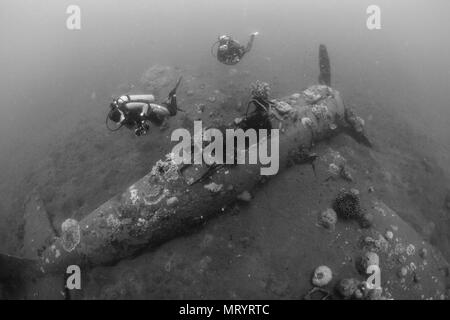 Scuba divers inspect an underwater airplane wreck named the 'Zero' lies on the sand in Kimbe Bay, Papua New Guinea - Stock Photo