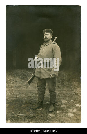 German historical photo: a soldier with a beer belly in military uniform in full gear with a rifle over his shoulder posing outside. world war one - Stock Photo