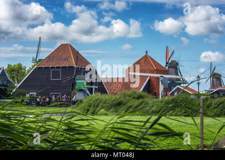 Zaandam, The Netherlands, August 4, 2017: Characteristic green houses and windmills on the Zaanse Schans. - Stock Photo