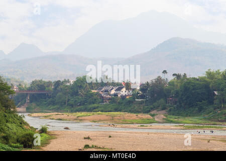 View of Nam Khan River at low tide and lush riverbank in Luang Prabang, Laos, on a sunny day. - Stock Photo