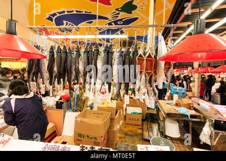 Indoor Omicho Ichiba, Omicho fresh food Market in Kanazawa, Japan. Large fish market store, with gutted fish hanging, sticks holding stomachs open. - Stock Photo