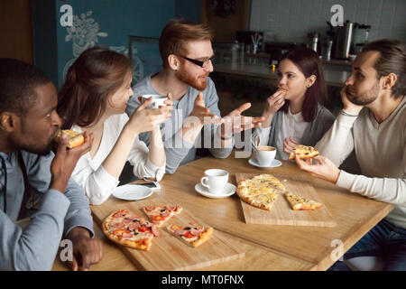 Redhead guy talking to diverse friends eating pizza in pizzeria - Stock Photo