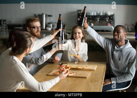 Diverse millennial people hanging out together drinking beer eat - Stock Photo
