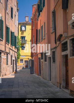 One of the many little side streets lined with colourful buildings in Venice, Italy - Stock Photo