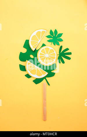 Popsicle from paper tropical leaves and orange slices on a bright yellow background - Stock Photo