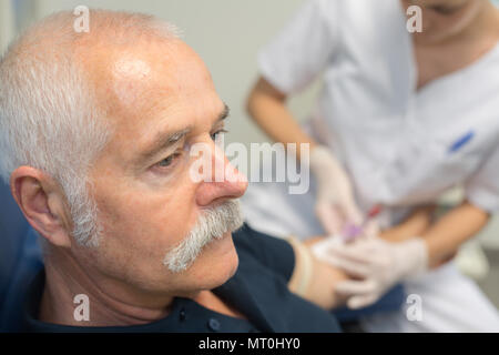 senior man receiving an insulin injection - Stock Photo