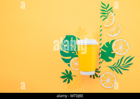 Disposable paper cup on a yellow background with tropical leaves and orange slices on a bright yellow background. Colorful summer drink concept with p - Stock Photo