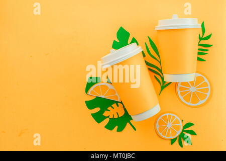 Disposable paper cup on a yellow background with tropical leaves and orange slices on a bright yellow background. Colorful summer drink concept with paper cut outs. - Stock Photo
